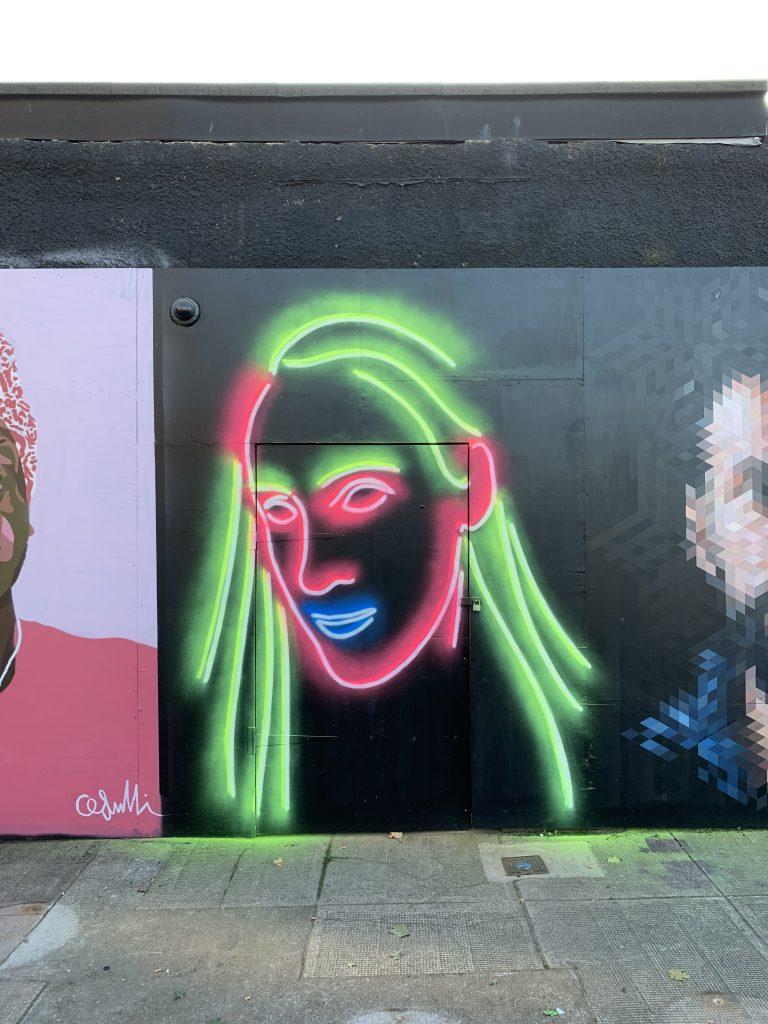 Neon face street art Clutha